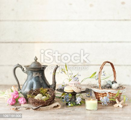 Vintage Easter Teapot, Tulips and Easter Eggs on an Old Rustic White Wood Background. Easter, Mother's Day Concept.