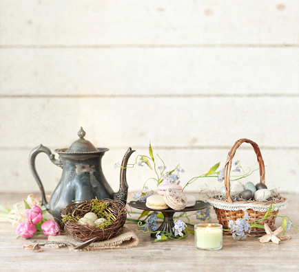 Vintage Easter Teapot, Tulips and Easter Eggs on an Old Rustic White Wood Background