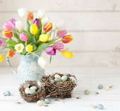 Vintage Easter Tulips and Easter Eggs on an Old White Wood Background