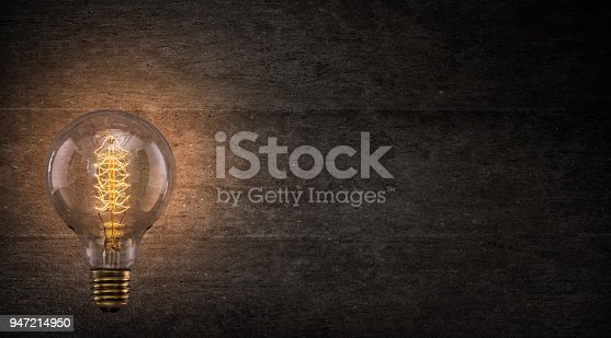Vintage Edison light bulb on dark background with empty space for text.