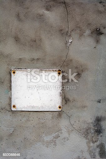 Vintage empty sign with great patina against old cemented wall with cracks