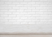 Vintage empty wooden table on defocused white brick wall background