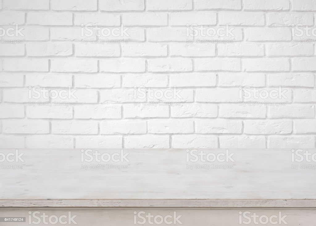 Vintage empty wooden table on defocused white brick wall background stock photo
