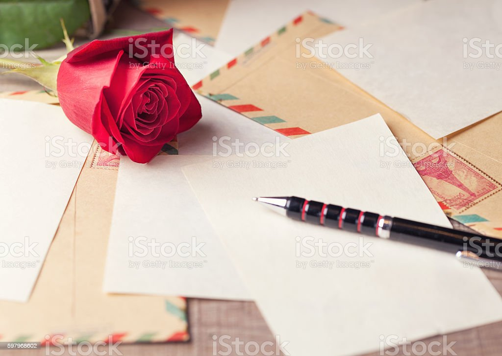 Vintage envelopes, red rose and sheets of paper stock photo