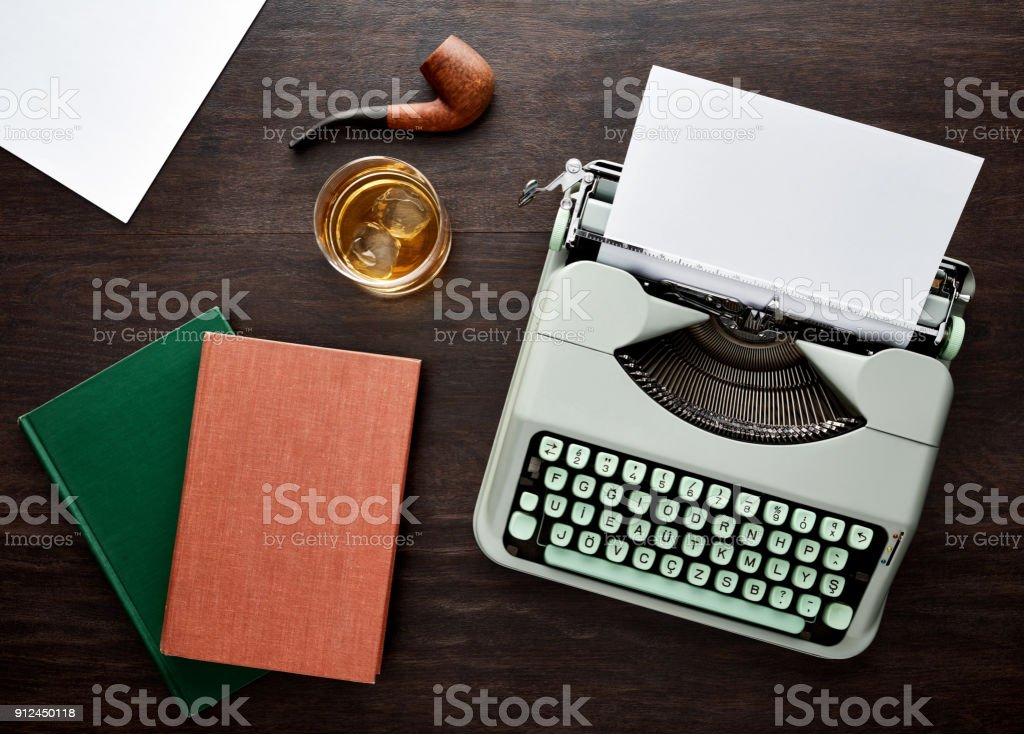 vintage f type typewriter blank papers pipe books and a glass of