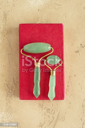istock Vintage face Jade roller on old red box  on beige concrete background. Natural tool for  lymphatic drainage and reduce the appearance of puffiness and wrinkles. 1249100661