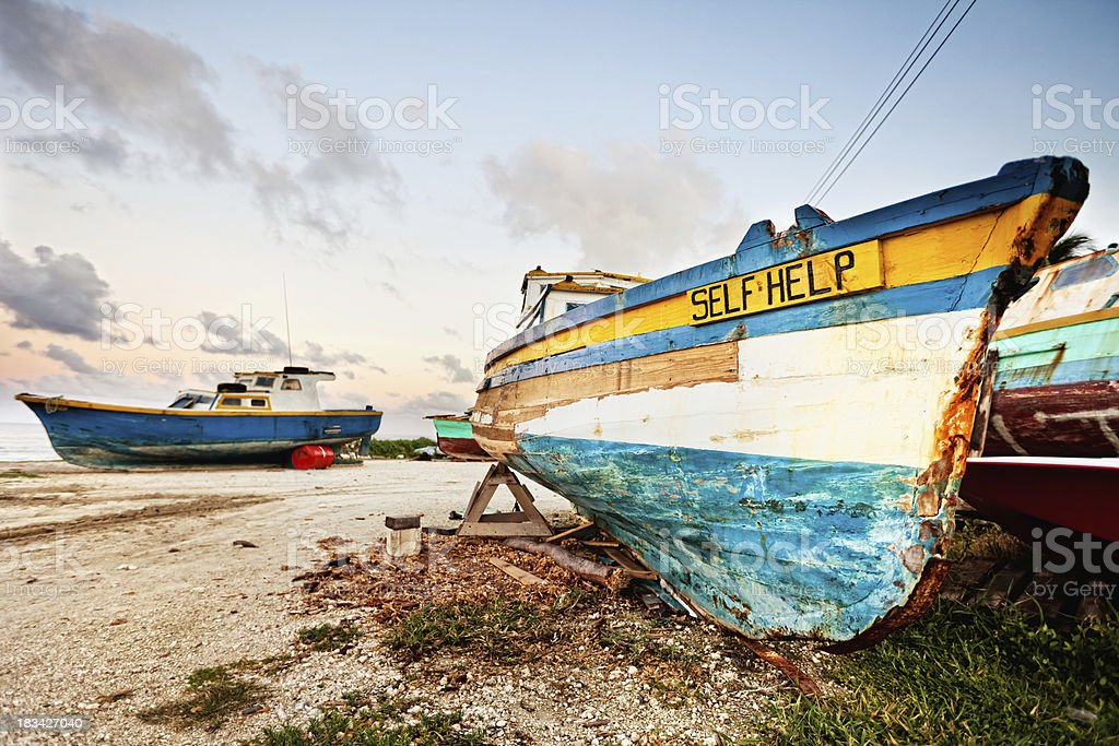 Vintage faded fishing boats on land stock photo
