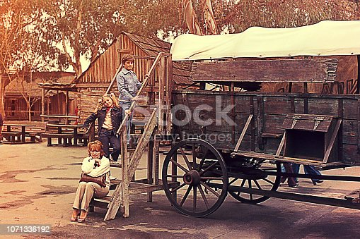 Vintage image of a mother and her child in front of an old wooden carriage.