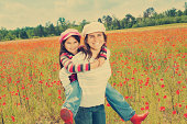 Vintage little girl, boy, mother playing on poppy field