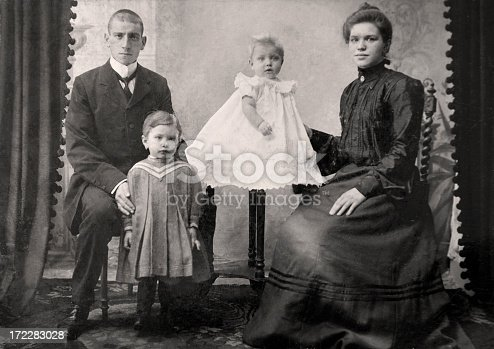 Young Couple posing in studio with their (first) two kids in the twenties.