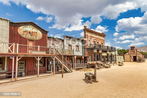 istock Vintage Far West town with saloon. Old wooden architecture in Wild West. 1305790910