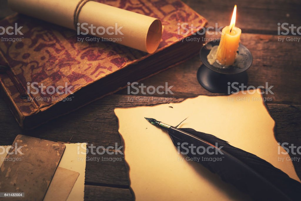 vintage feather with paper and old book on table stock photo
