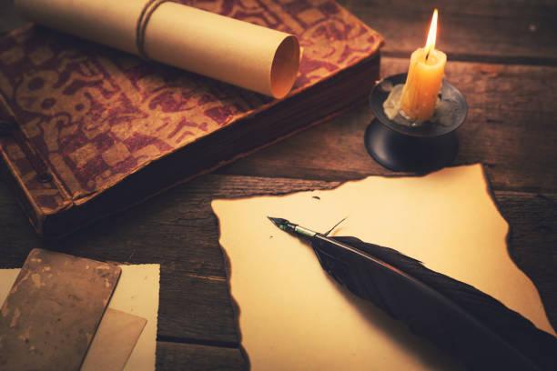 pluma vintage com papel e livro velho na mesa - foto de acervo