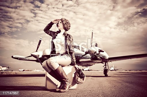 Horizontal portrait of a young woman dressed in 40's aviator attire, sitting on a suitcase on the run way with her plane.