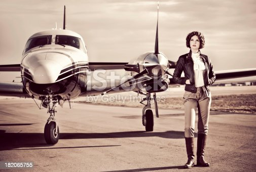 Horizontal portrait of a young woman dressed in 40's aviator attire stands on the run way with her plane.Image is processed from a 16 bit RAW file and profiled in ProPhoto RGB. All my images are professionally retouched.**Need more shots from this series: