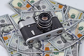 Vintage film camera on scattered American dollars. Concept of earning on photo stocks.