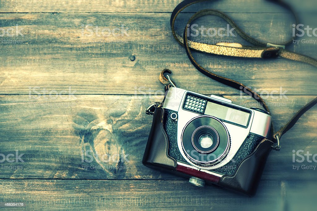 Vintage film camera on wooden background. Instagram style stock photo