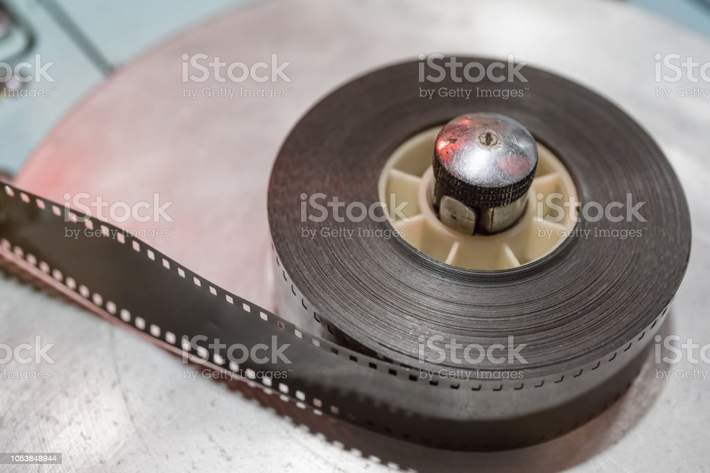 Vintage film reel or tape on a roller. stock photo