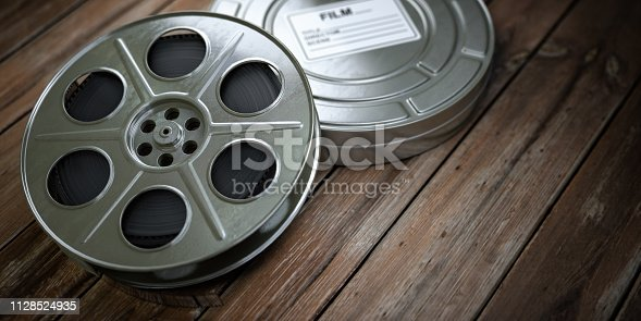 istock Vintage film reel with filmstrip on wood background. Video, cinema, multimedia concept. 1128524935