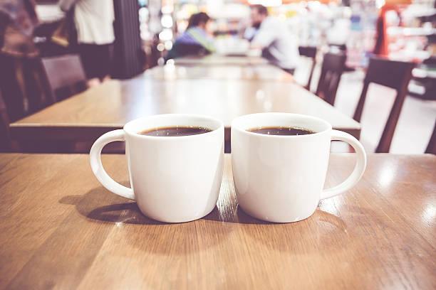 Vintage filtro, casal de branco, xícara de café na mesa de madeira - foto de acervo