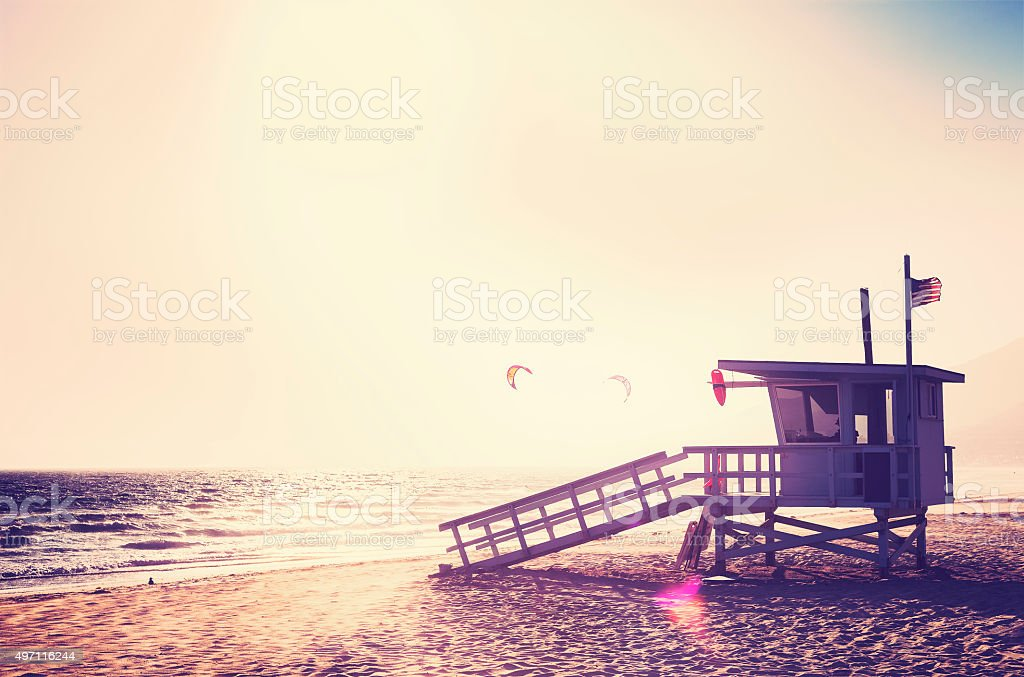 Vintage filtered lifeguard tower at sunset. stock photo
