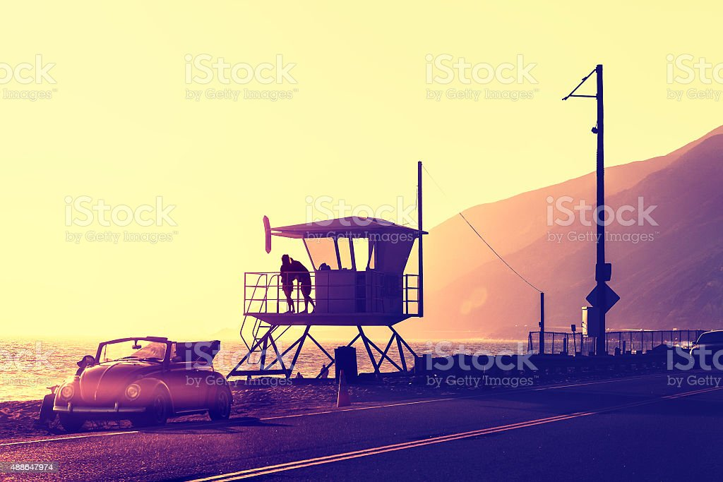 Vintage filtered sunset over beach with lifeguard tower. stock photo