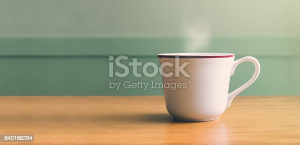 istock Vintage filter,Hot white coffee cup on wood table with blur pastel green wall with sun light from right side,Leave copy space for adding your text or design 840186294