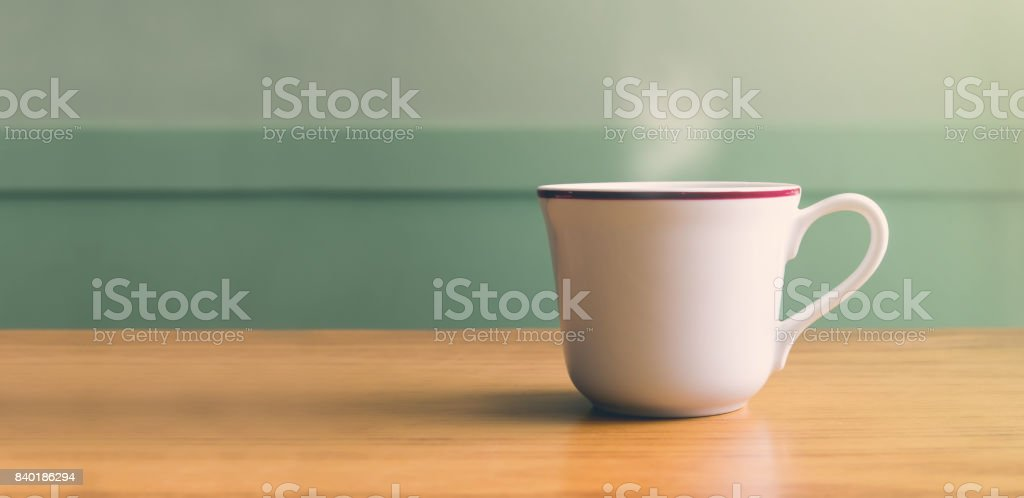 Vintage filter,Hot white coffee cup on wood table with blur pastel green wall with sun light from right side,Leave copy space for adding your text or design stock photo
