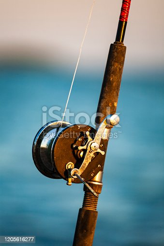 Vintage fishing rod and reel close up outdoors.