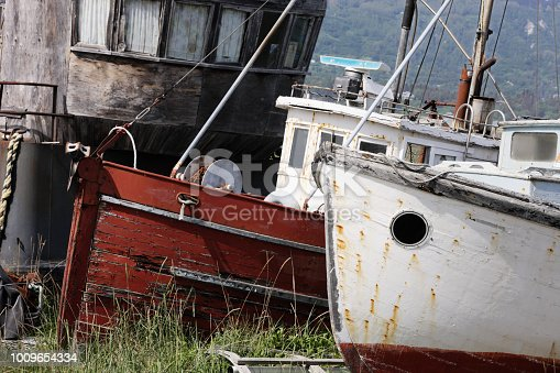 Old wooden fishing trawlers drydocked on land with deteriorating hulls, neglected for newer ships.  Three vessel bows diagonnlly in a row, closely cropped.