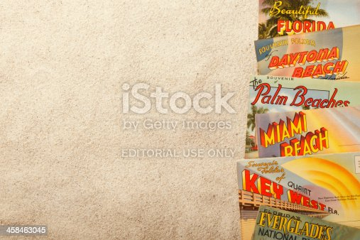 San Diego, California, USA - November 19, 2013: A group of vintage postcards showing various Florida tourist destinations on top of beach sand. Sot in a studio setting on a tan background.