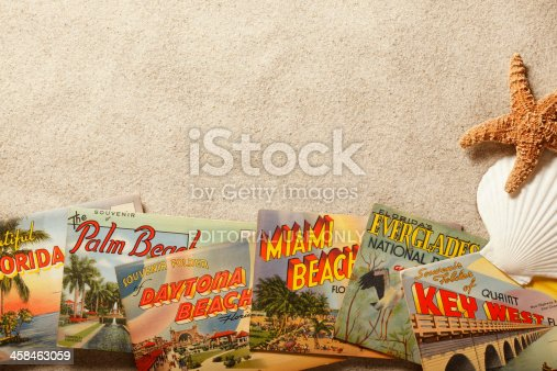 San Diego, California, USA - November 19, 2013: A group of vintage postcards showing various Florida tourist destinations on top of beach sand with starfish and shells. Shot in a studio setting on a tan background.