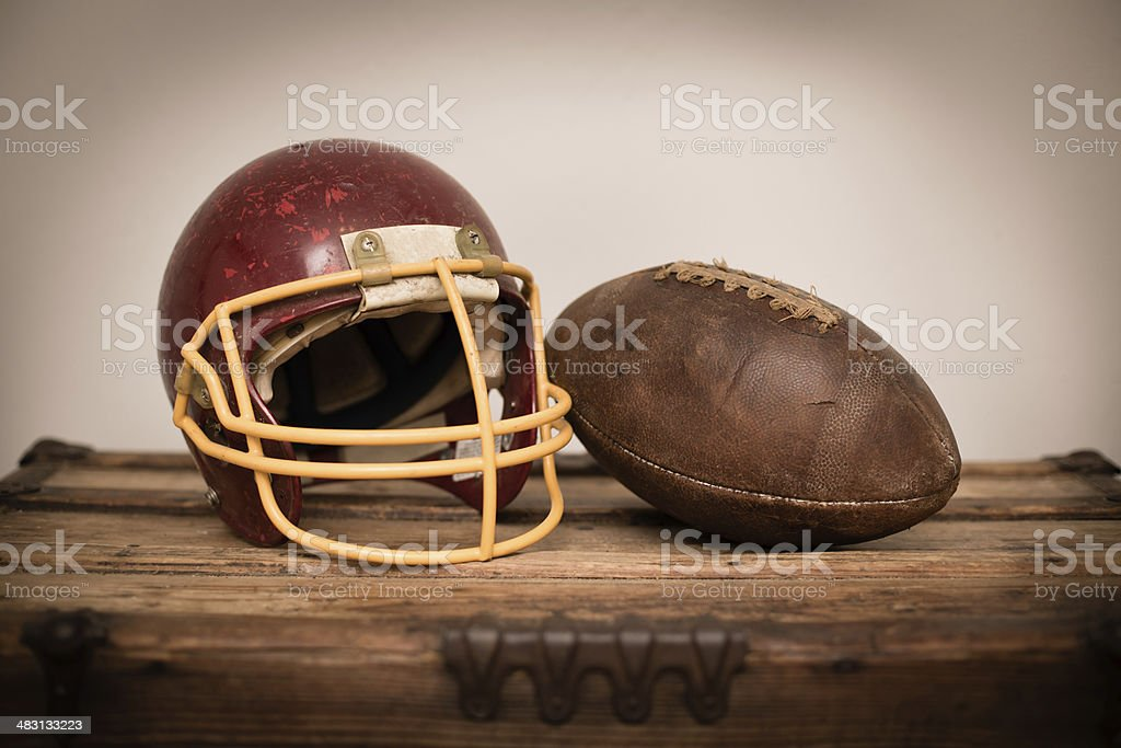 Vintage Football and Helmet, Sitting on Old Wood Trunk royalty-free stock photo