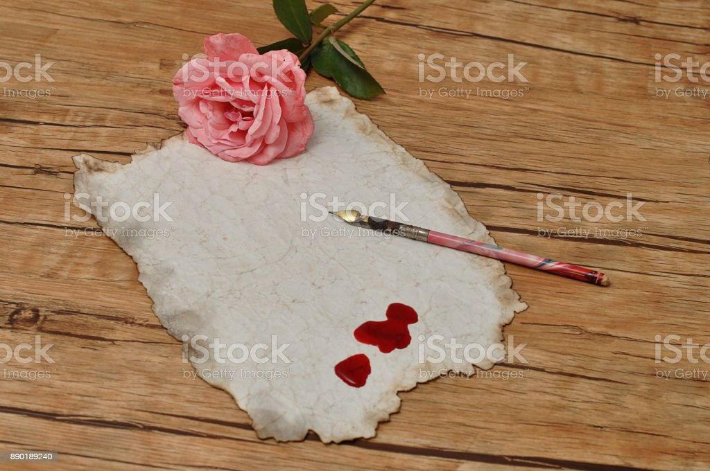 A vintage fountain pen with old paper with drops of blood and a pink rose stock photo