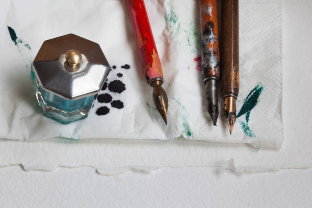 Vintage fountain pens with inkwell blotter napkin. White paper textured background. Artist workshop concept. close-up, up view Vintage fountain pens with inkwell blotter napkin. White paper textured background. Artist workshop concept. close-up, up view photo blotter stock pictures, royalty-free photos & images