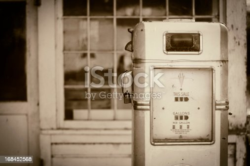 An old gas station fuel pump. Shallow depth of field. Sepia toned image, vintage processing.