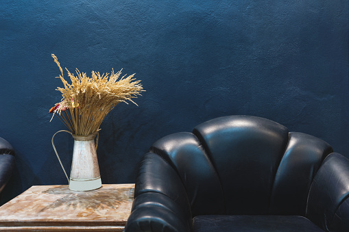 Vintage furniture and decoration, Dark blue wall with part of vintage leather armchair and vase with flowers on side table