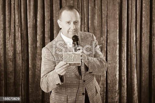 A vintage processed game show host holding a microphone. Photographed in studio with a purpose built set and props.
