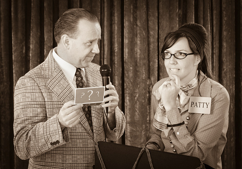 A vintage processed game show host and contestant. Photographed in studio with a purpose built set and props.