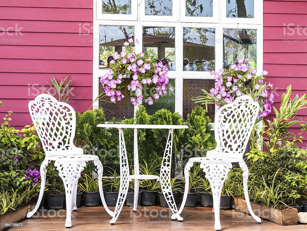 Vintage garden with white tea table and chairs stock photo