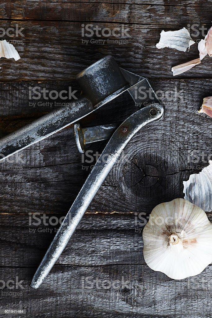 Vintage garlic press on old wood backgorund stock photo