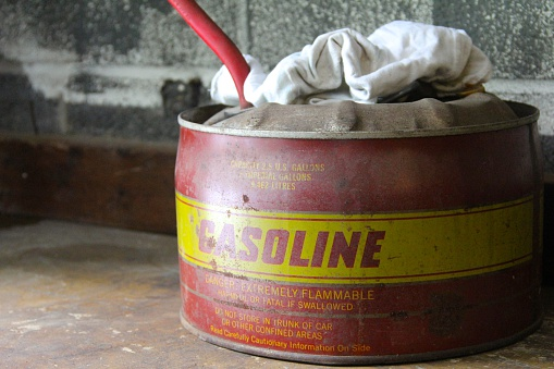 This is an old and worn out antique gasoline can and white rag set on a  wooden shelf.
