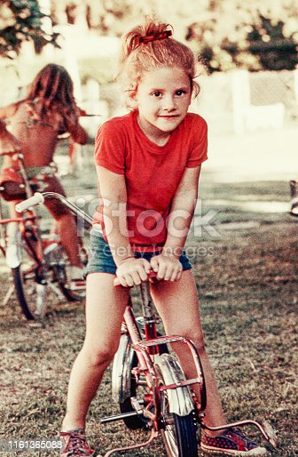 Vintage photo of a cute blonde girl on her little bike