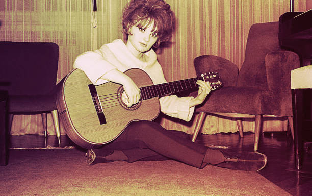 vintage girl playing guitar at home - 1960s style stock photos and pictures