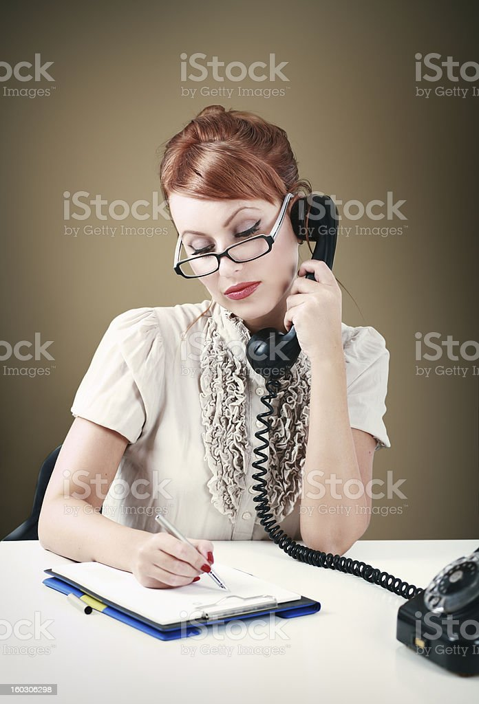 Vintage cross processed photo of a young redhead secretary making a...