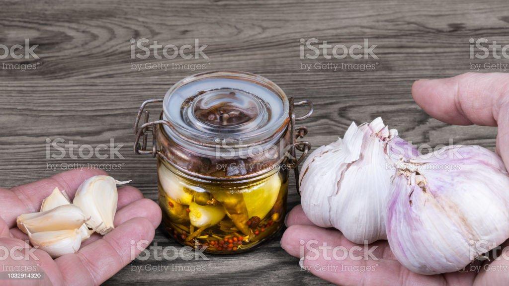 Vintage glass jar and hands with aromatic garlics. Allium sativum stock photo