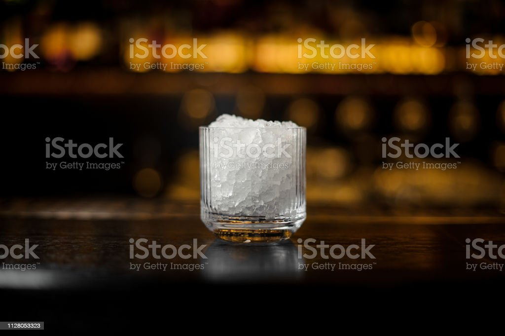 Vintage glass of crushed ice standing on the empty steel bar stand on...