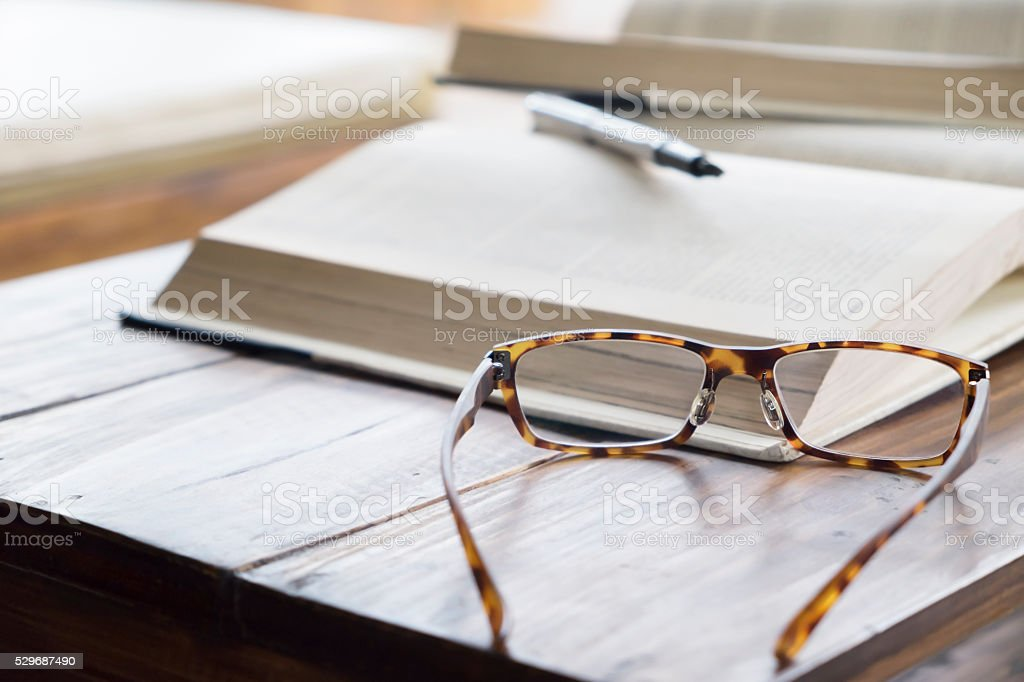 Vintage glasses on opening book in library or cafe. stock photo