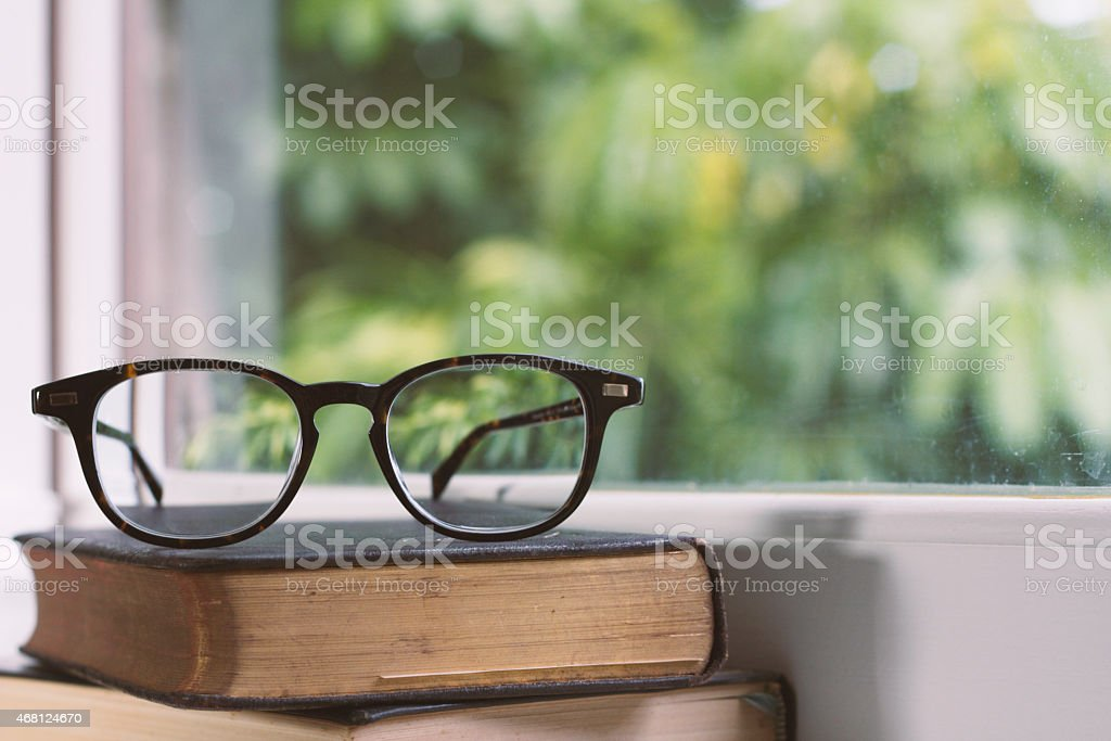 Vintage glasses sitting on leather-bound books next to a window stock photo