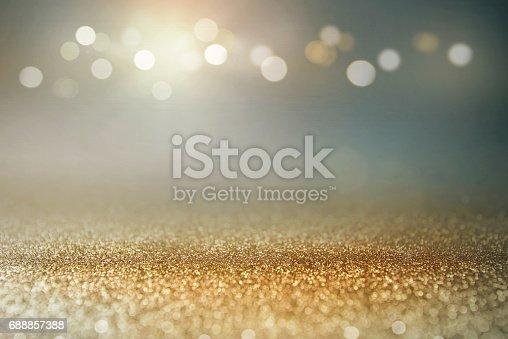 613518332 istock photo Vintage glitter gold, dark blue and black lights bokeh background. 688857388